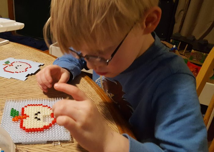 Five Year Old Boy Focusing On Bead Placement on a board from Zirrly Super Beads Mega Pack with apple template in a product review of Zirrly