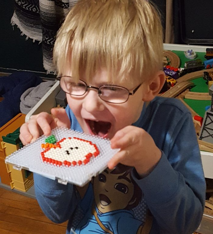 Blond boy with glasses pretending to eat a plastic bead apple he designed with Zirrly Mega Pack of Super Beads in a product review