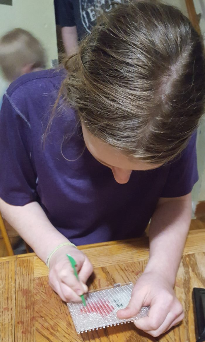 Teen girl removing her dried Super Bead design from the plastic board in product review of Zirrly Super Beads
