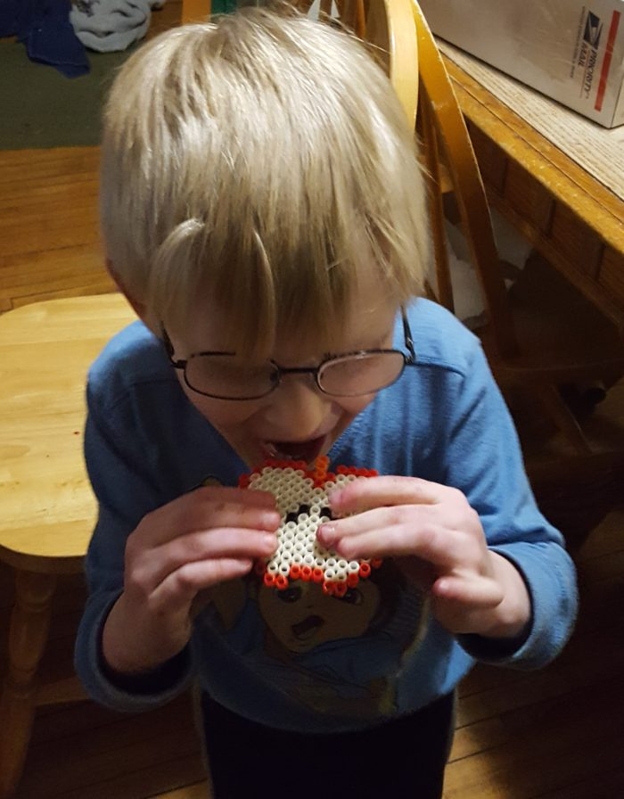 Young blond boy with glasses and blue shirt pretending to eat a Zirrly Super Bead finished apple design in a product review