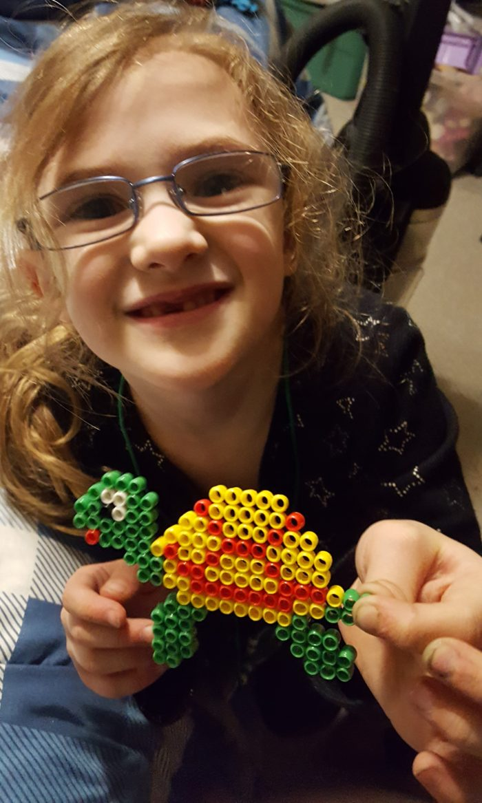 Young blond girl with glasses and missing front tooth holds up her Zirrly Super Bead design finished turtle in a product review of Mega Pack