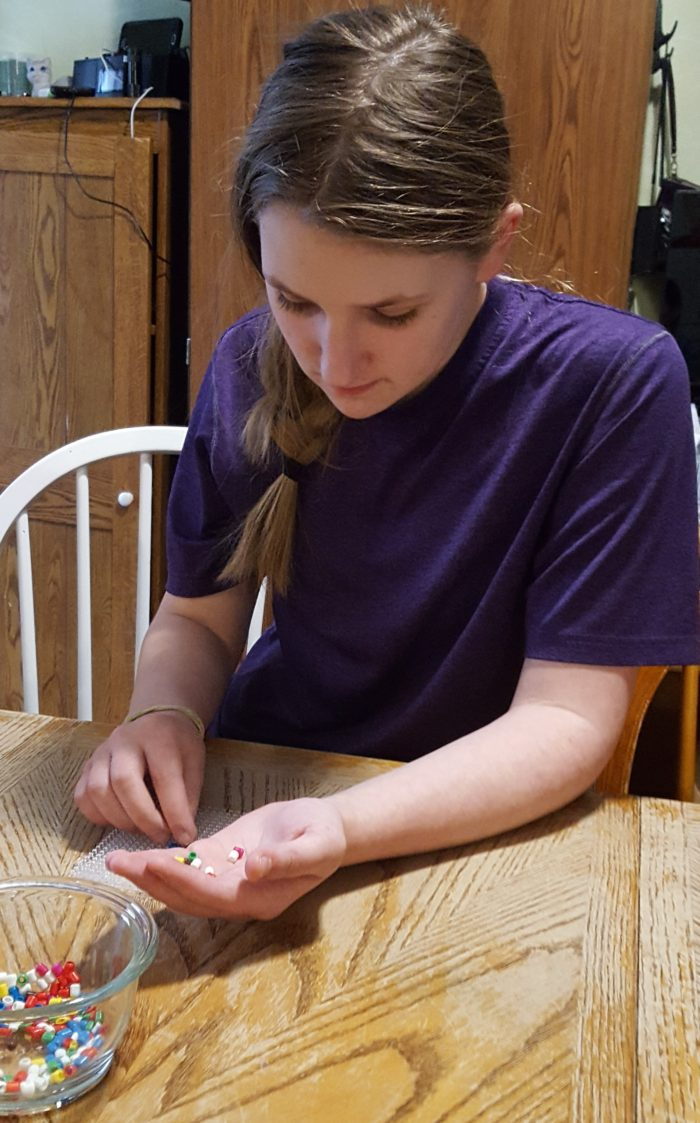Teen girl finding the right colors of bead to put on her design board in a product review of Zirrly Super Beads