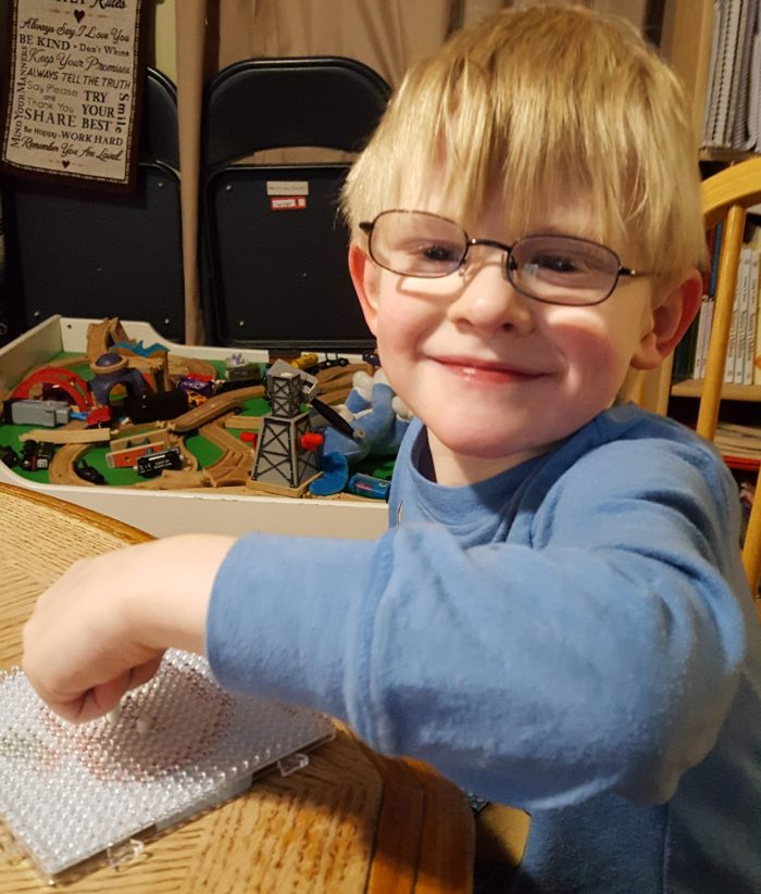 Young blond boy with glasses placing beads on a plastic board with train table background product review super beads