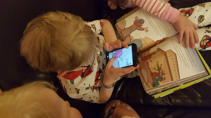 Planet 316 Story Bible App used by a young boy in glasses while siblings look on