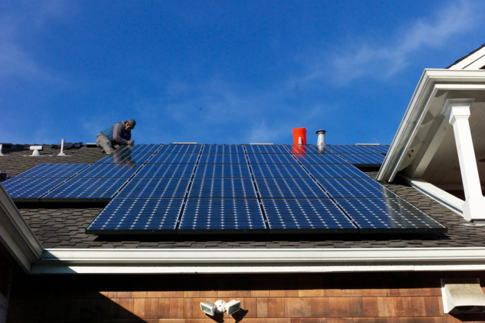 Off Grid Solar Panels for your home man on roof installing solar panels