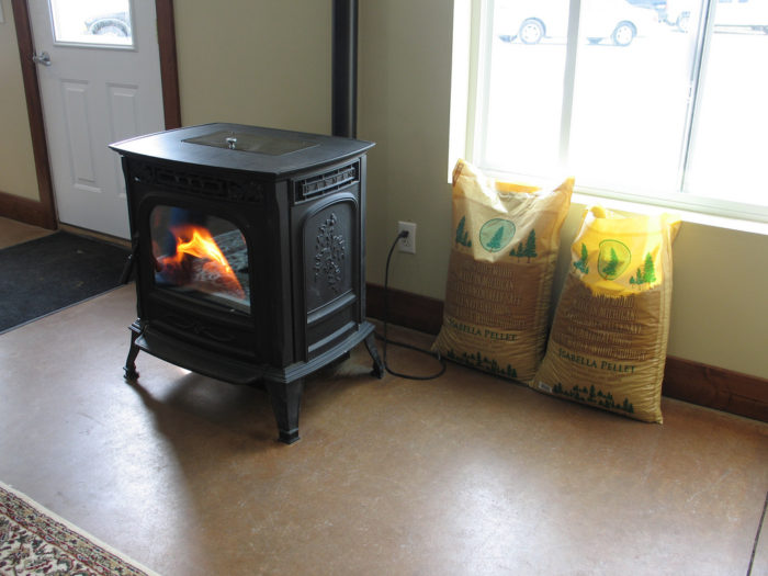 Off-Grid Heating with an electricity powered pellet stove burning wood pellets near bags of pellets in a home near the front door