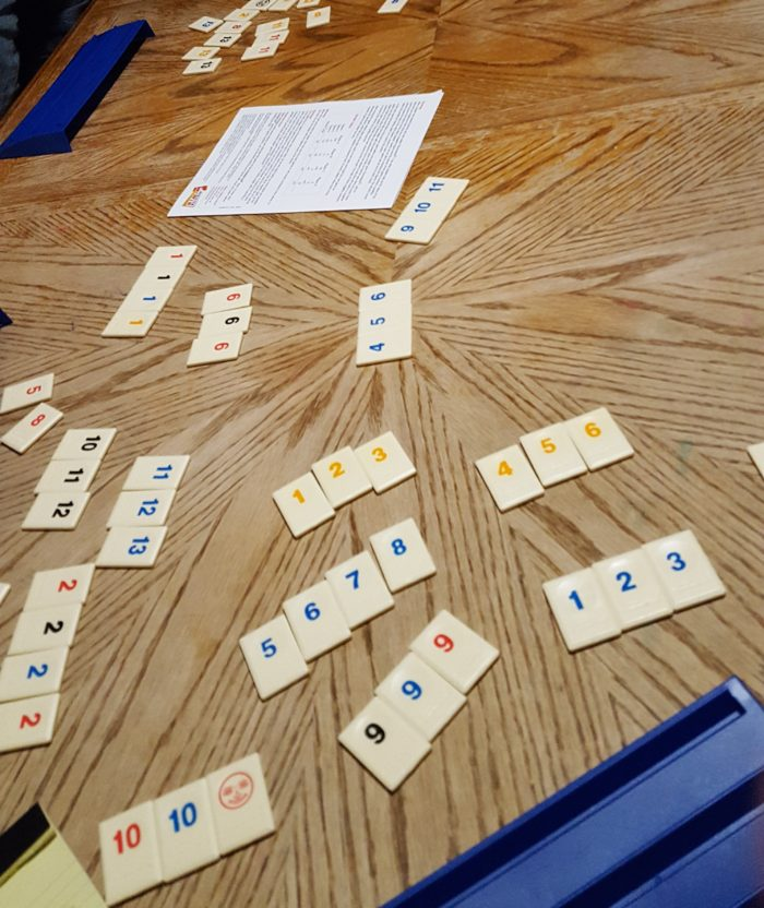 Playing Rummikub at our big dining room table in a review of Goliath Games