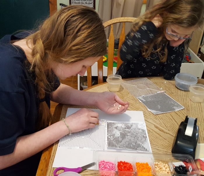 Goliath Games - Photo Pearls review teen girl and young girl placing beads on tray according to the pattern