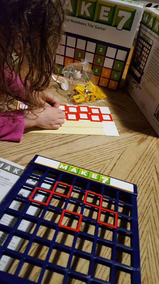 review of Make7 young girl places red stickers onto game structure