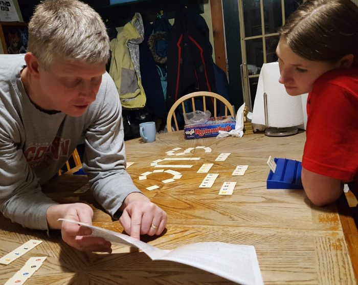 Dad reading rules to his teen daughter playing Rummikub