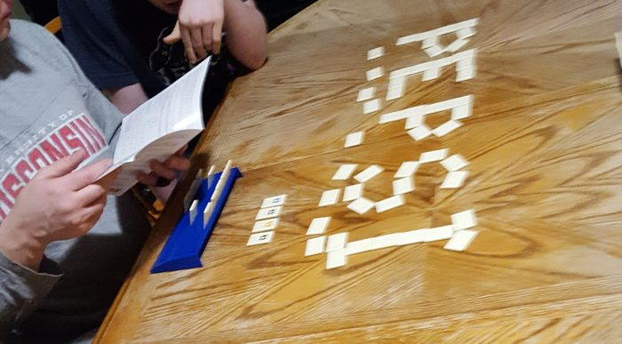 Dad and teen son figuring out how to play Rummikub boy spelled Pepsi on table with tiles