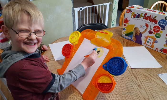 review of Paint-Sation young boy is painting on his easel