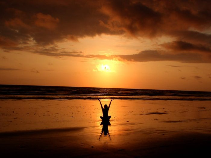 Self-Improvement person on a beach with hands up at sunset sunrise