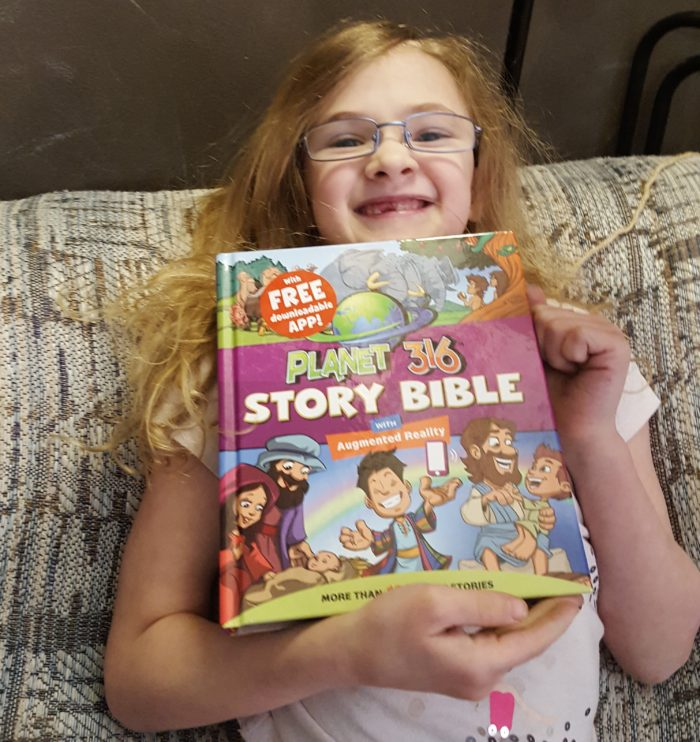 Planet 316 young girl holding her new story bible for all to see