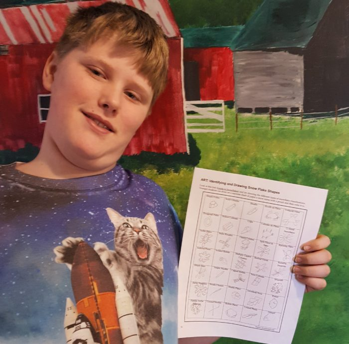 a teen boy showing his snow shape drawings from a homeschool unit study on snow