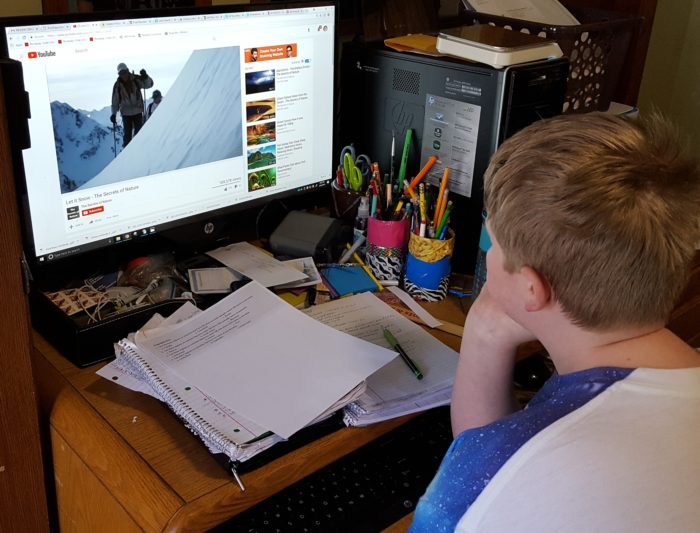 a preteen boy watches a YouTube video Let It Snow for a creation unit study on snow from Creation Illustrated Magazine
