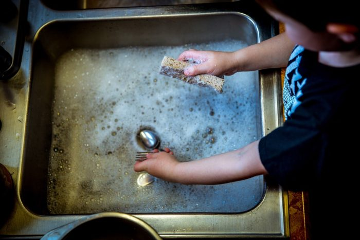 Clean In Just A Few Hours child washing dishes in stainless steel sink