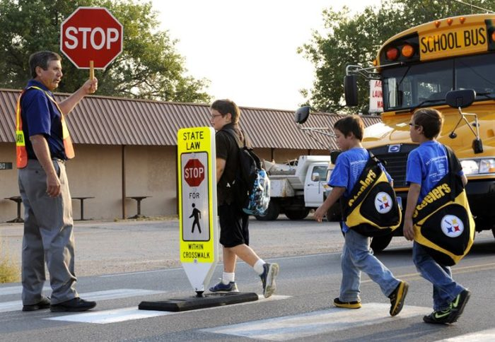 Teach kids about pedestrian safety image school bus stop crossing guard holding a sign kids crossing the street with safety guard