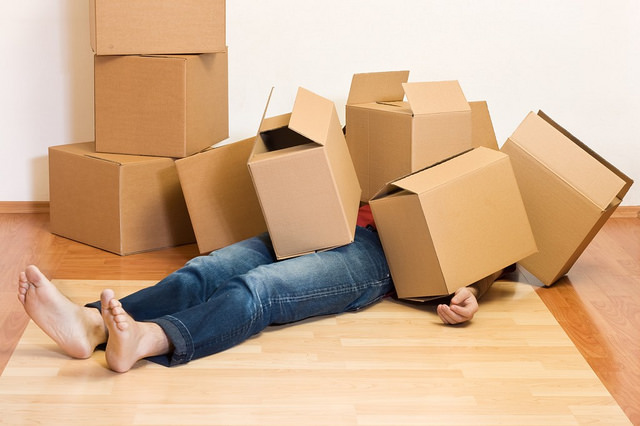 Moving house image person on floor covered in moving boxes