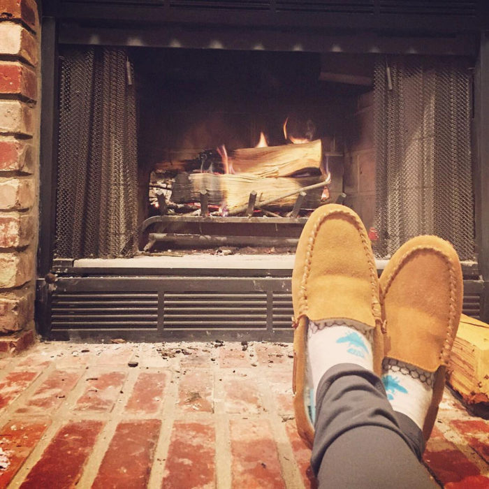 Home into a paradise image of person's feet with moccasin slippers near fireplace