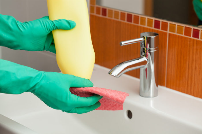 10 Terrific Hacks That Will Transform Your Home into a Paradise image hands in rubber gloves pouring cleaner onto sponge in preparation for cleaning