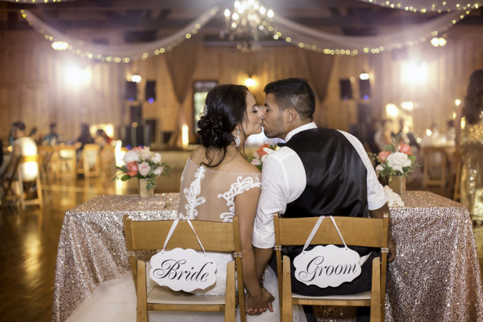 Bella Springs Wedding Venue image interior wedding reception decorated with lights and tulle bride and groom kissing