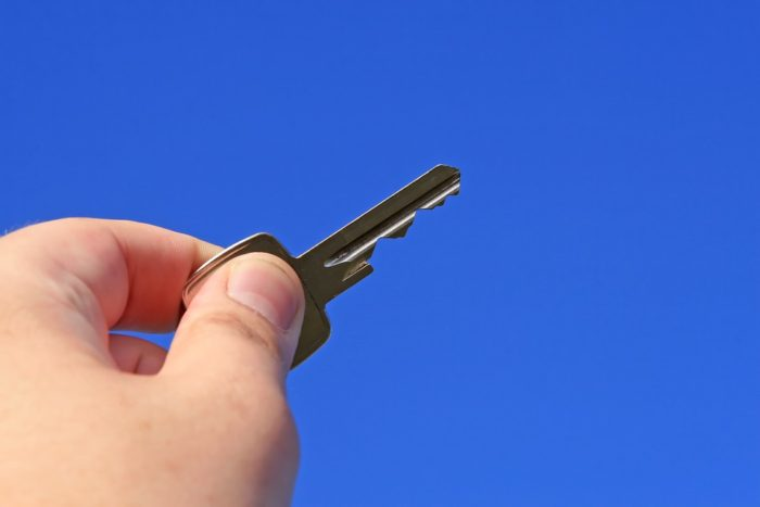 Moving could be the wrong option hand holding key blue sky