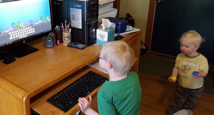 Review of ASD Reading computer program for autism spectrum disorder image of boy using computer with toddler boy holding balls watching his brother