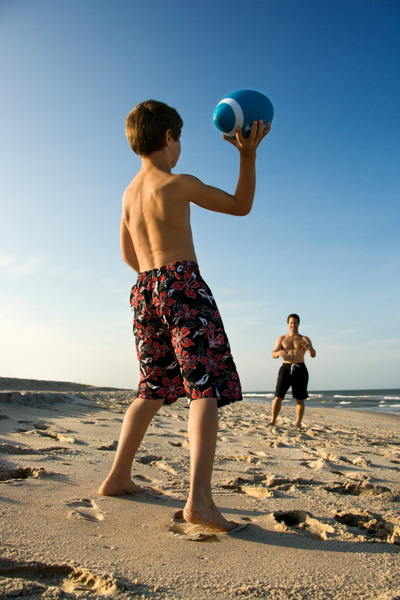 Large family camping trip image boy playing football with dad on the beach at the campground