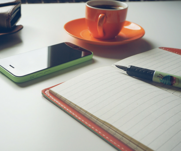 Blogger outreach image coffee paper pen phone on desk