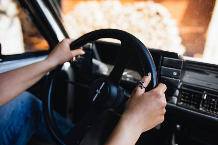 Insurance Coverage - Auto Insurance image person's hands on steering wheel in an automobile