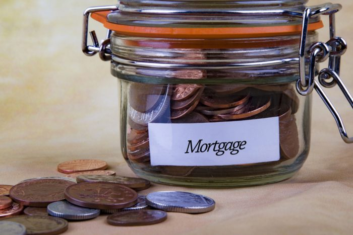 Coping with your mortgage payments - image glass jar with coins mortgage