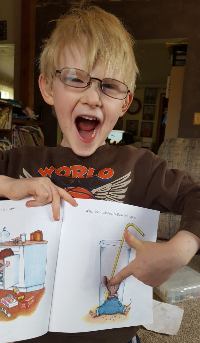 Home School Navigator Level Red Reading image of young boy in glasses pointing to the mouse in his book