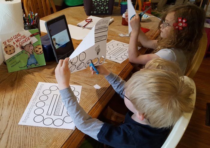 Home School Navigator image of children at a table cutting worksheet pages while watching iPad video for Level Red