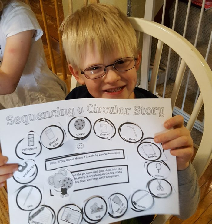 Home School Navigator image of boy with glasses holding his completed worksheet for Level Red