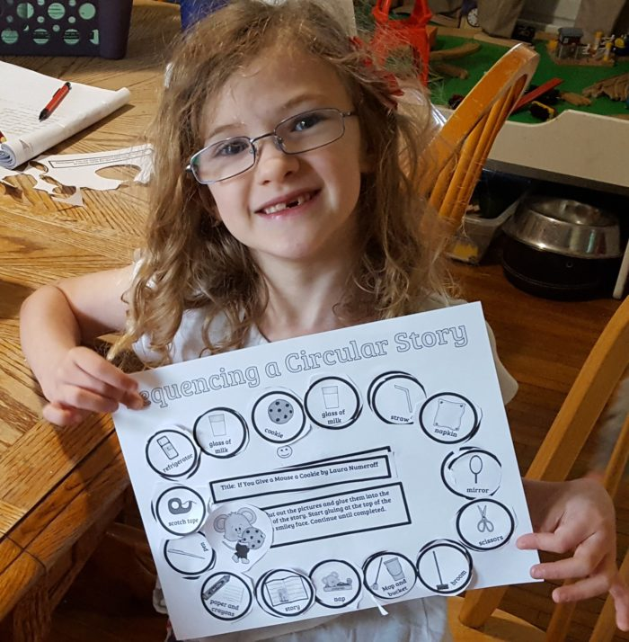 Home School Navigator image young girl in glasses shows her completed worksheet for Level Red