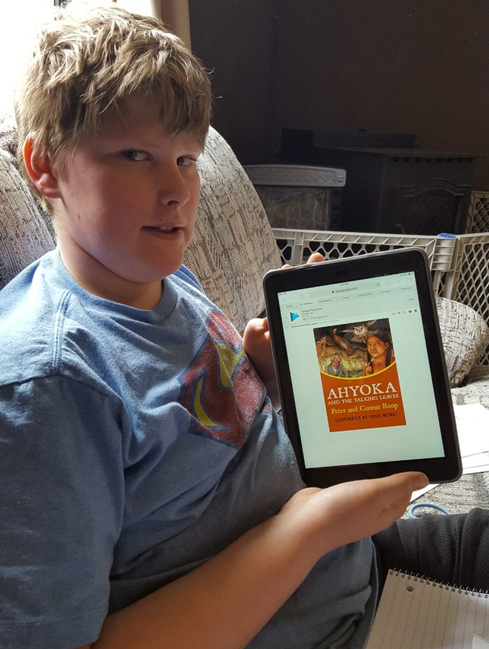 Home School Navigator image pre teen boy using iPad to read Ahyoka and the talking leaves ebook for Level Green