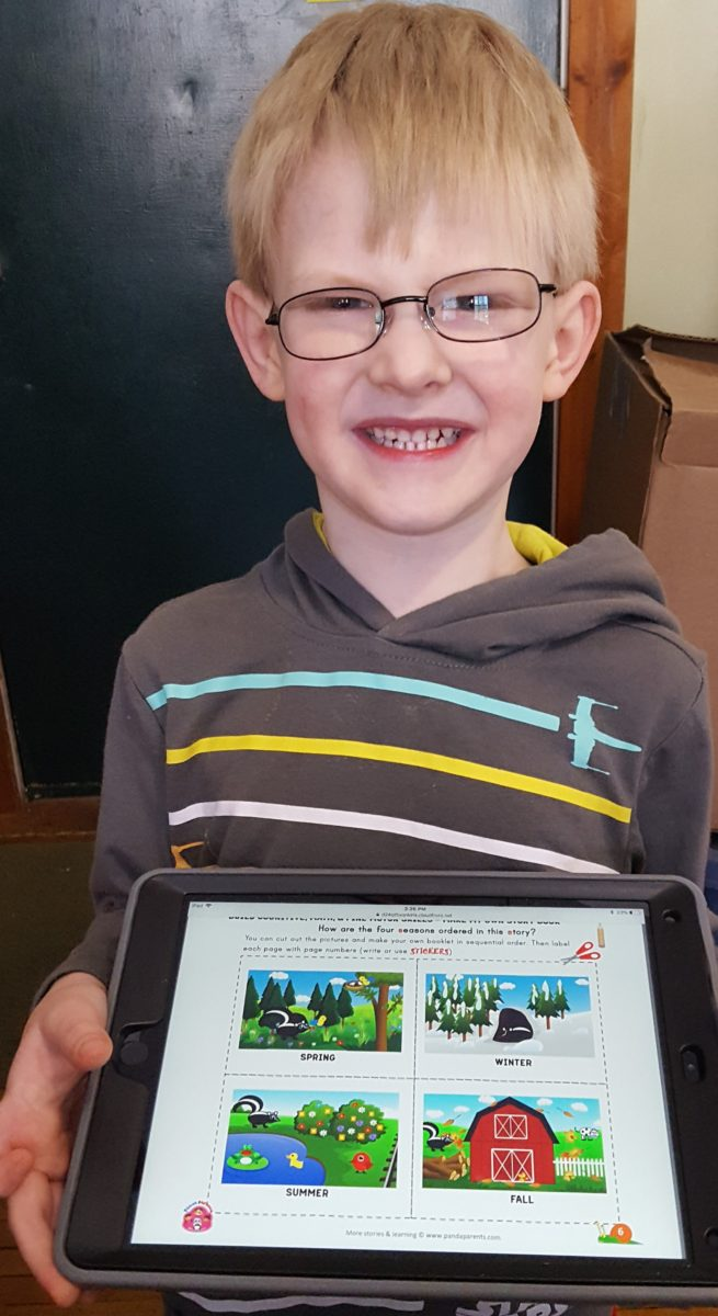 PandaParents product review image boy in glasses holding iPad showing a work page he can print out and do