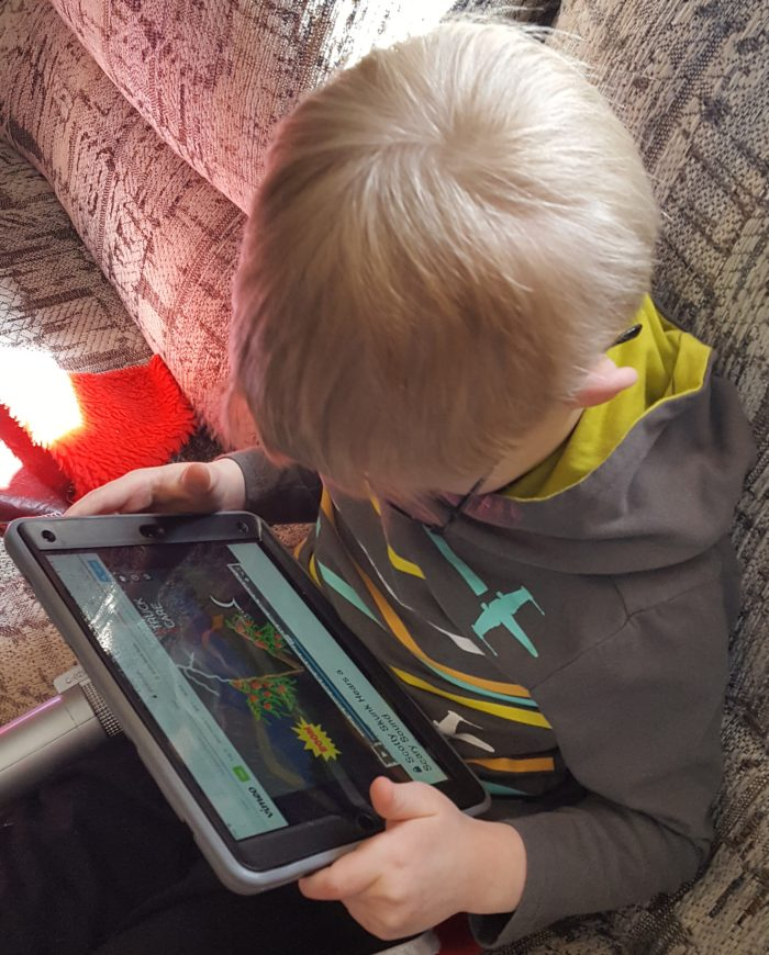 PandaParents Product Review image boy with glasses hearing a story be read to him on the iPad