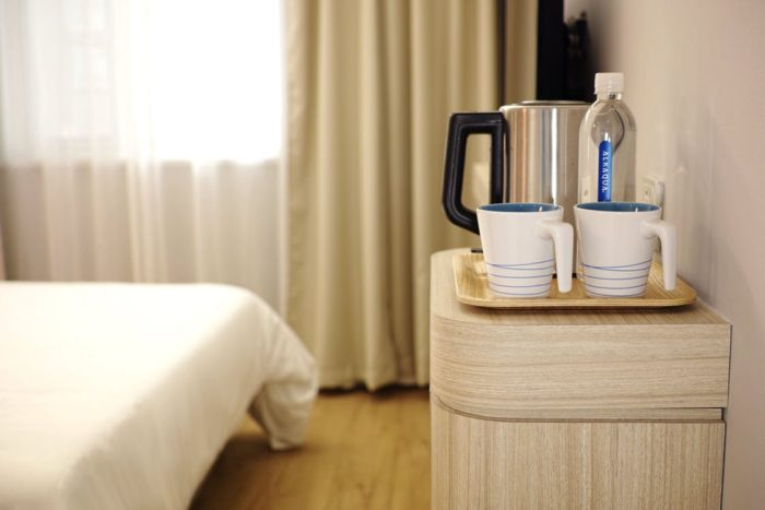 Making Guests Feel Welcome image of guest room with bed blackout curtains table with carafe coffee mugs bottled water