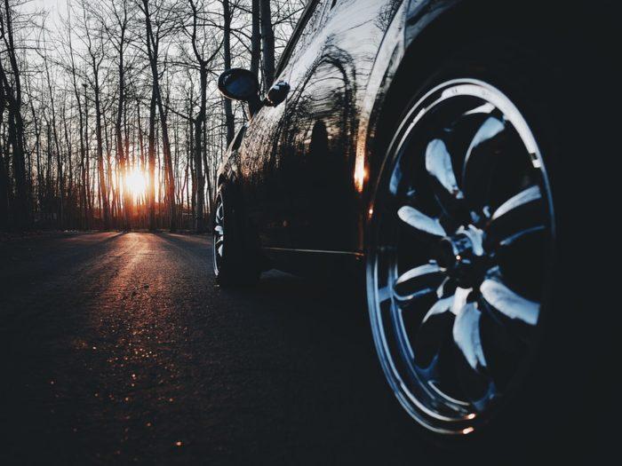 Responsible Road User image sedan car driving on road towards sunset