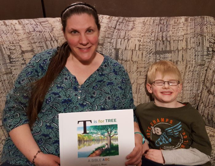 T is for Tree: A Bible ABC book review image mother and son holding a new book they are about to read