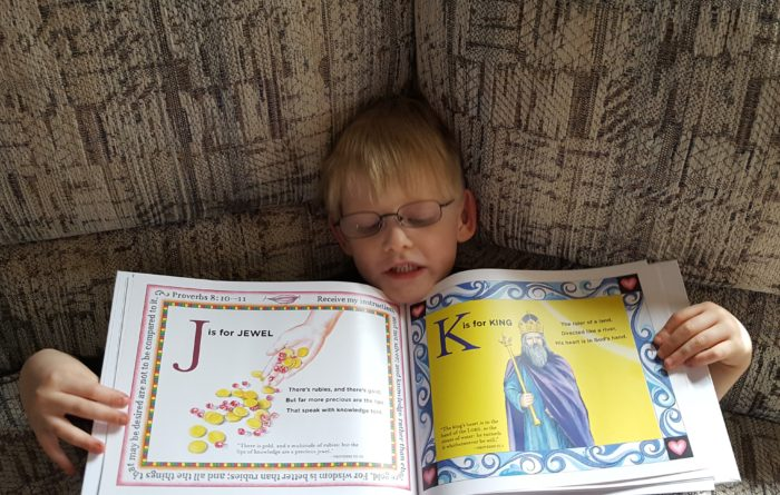 T is for Tree: A Bible ABC book review image boy with glasses holding the book open to the J is for Jewel and K is for King pages