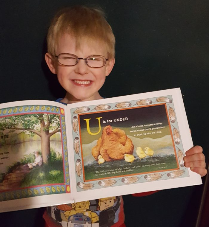 T is for Tree Book Review image boy in glasses and big smile holding book with U is for Under page showing