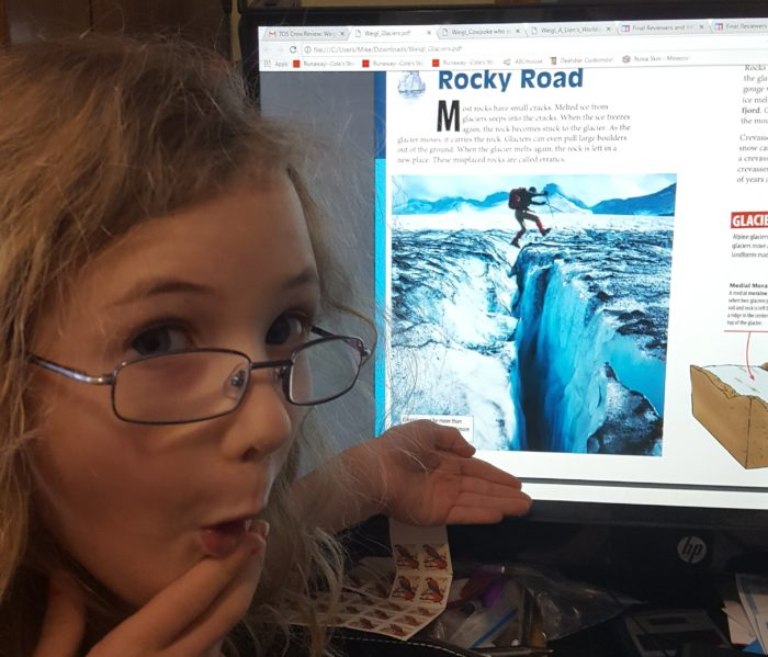 Weigl Publishers Glaciers eBook on the computer screen with young girl in glasses worried the guy might fall