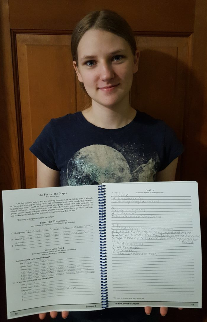 Classical Composition Fable and Narrative Product Review of Memoria Press Teen girl holds her completed work pages from Fable of The Fox and the Grapes