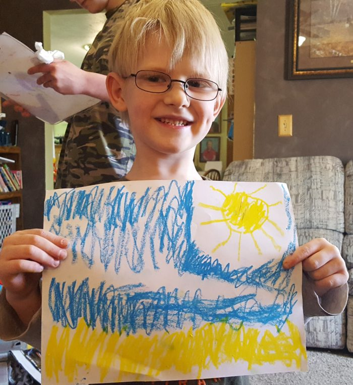 Product Review of ARTistic Pursuits image young boy in classes proudly holds up his art picture