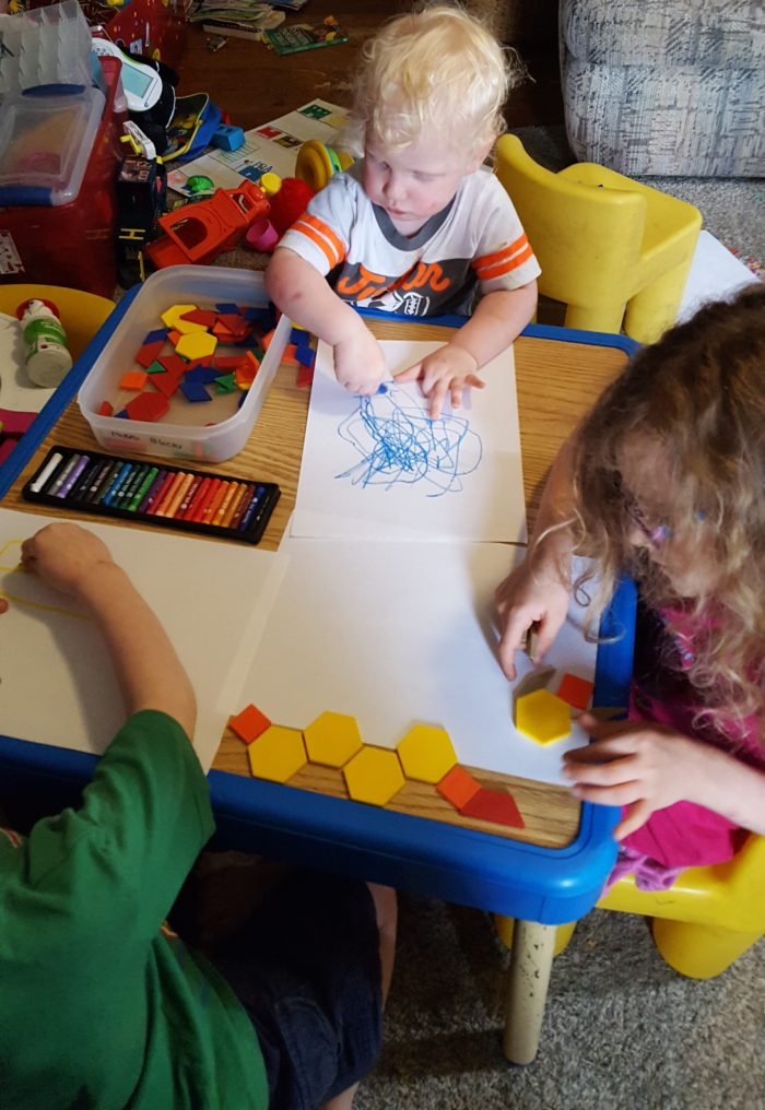 Product Review of ARTistic Pursuits image three small children at a table with shapes oil pastels and paper making art