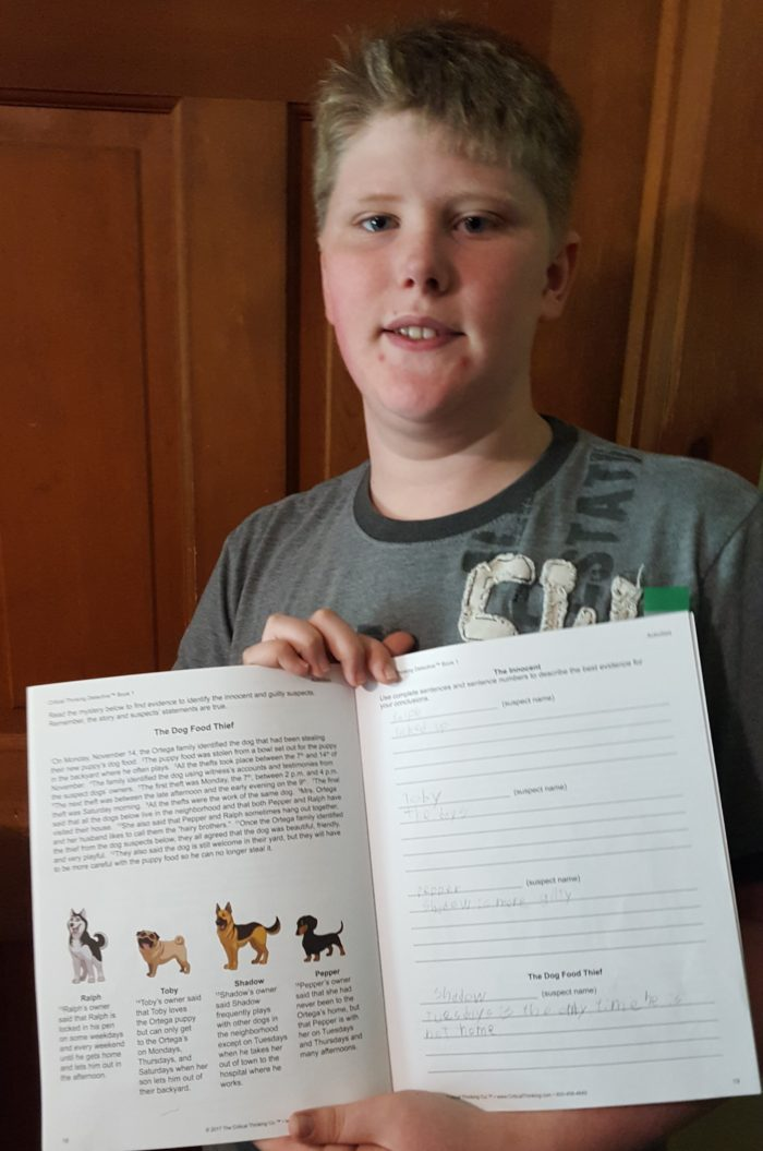 Critical Thinking Detective Book 1 review teen boy holding up a set of pages he did to complete a logic problem puzzle