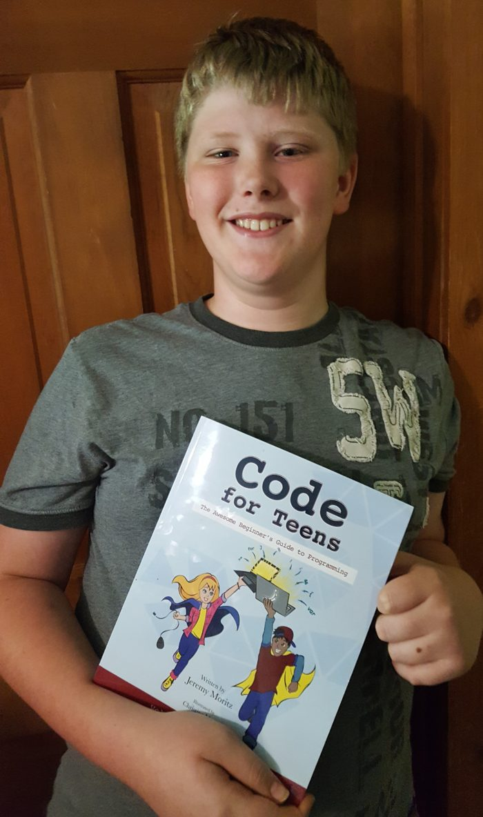 Code for teens image of a teenager holding his coding JavaScript book